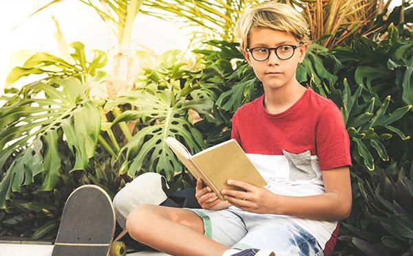 boy child eyeglasses outside reading